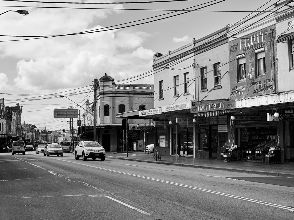 Enmore Road stretches across the frame, with the facade of Azzi's fruit shop visible to the right