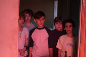 Five of 'the losers' stand in a doorway, looking into a red-lit room.