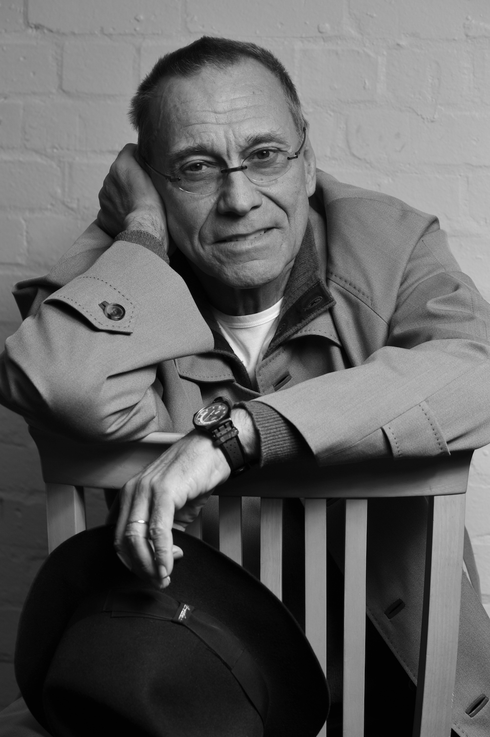 Andrei Konchalovsky sits backwards on a chair, looking at the camera.
