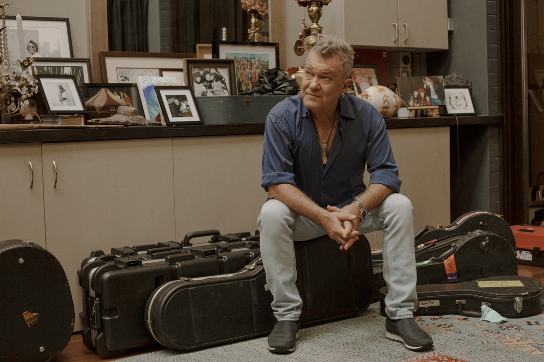 Jimmy Barnes sits on his guitar in front of a row of cupboards in his Sydney home. Many, many photos in frames sit on top of the cupboard.