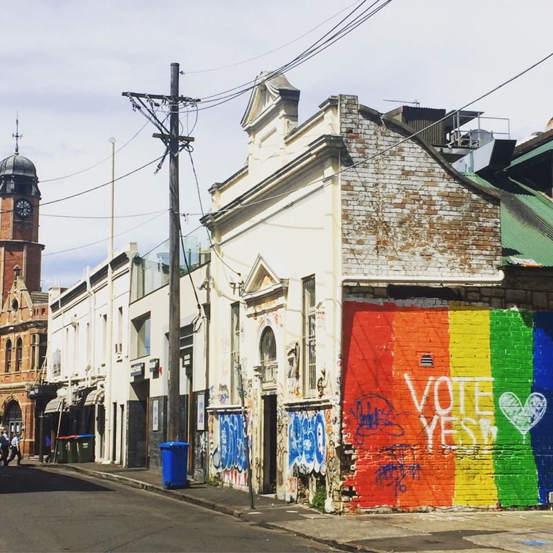 "A laneway in Newtown. The side of the closest building is painted the colours of the rainbow, with the words ""Vote Yes"" written on top."