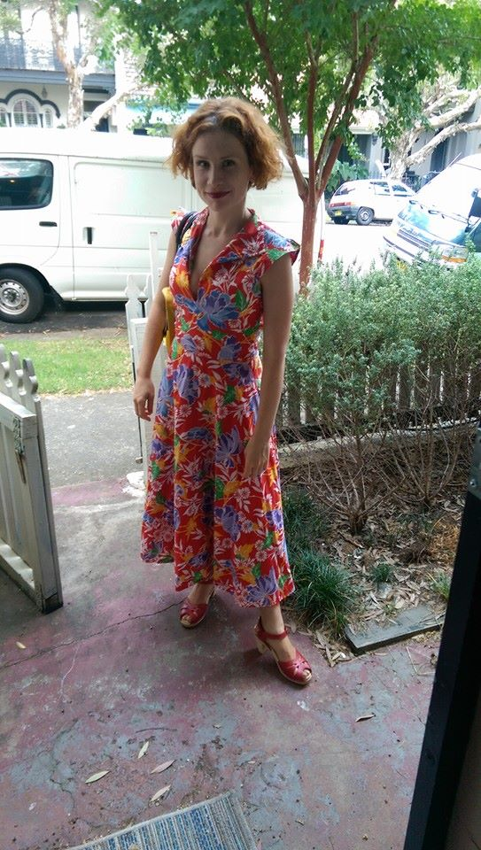 Fiona Wright stands inside the gate of her Newtown home in a colourful, full-length dress.