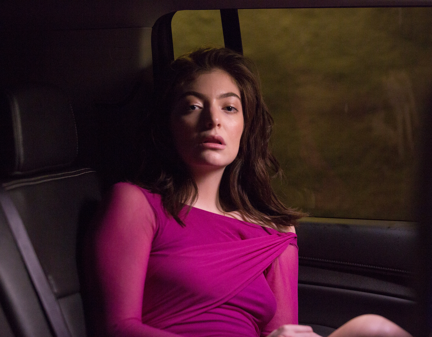 Lorde in the back of a car, looking directly into the camera.