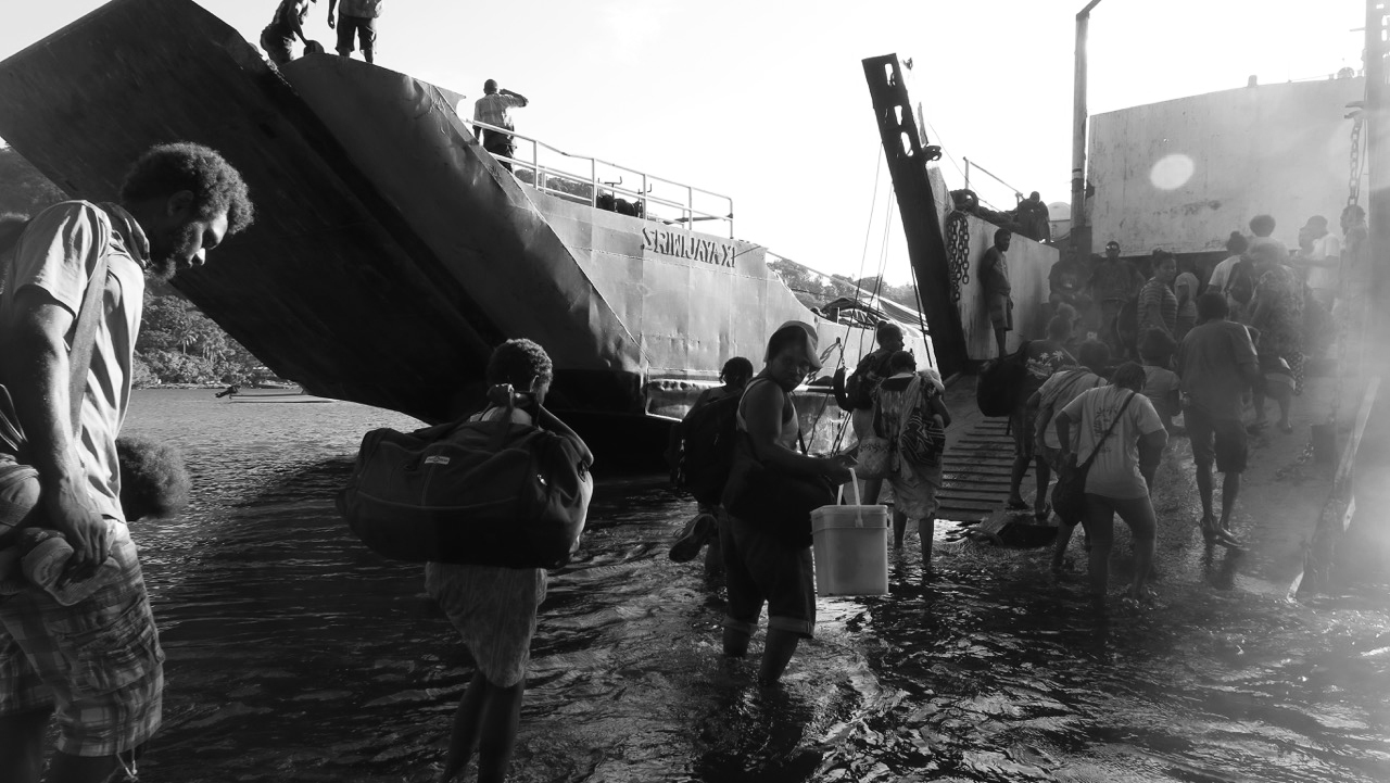 Dozens of tired-looking people wade through water and up the ramp of a barge.