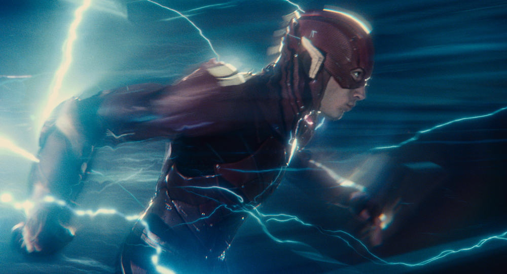 Close up of The Flash running: his outline is blurred and blue lightning streaks around him.