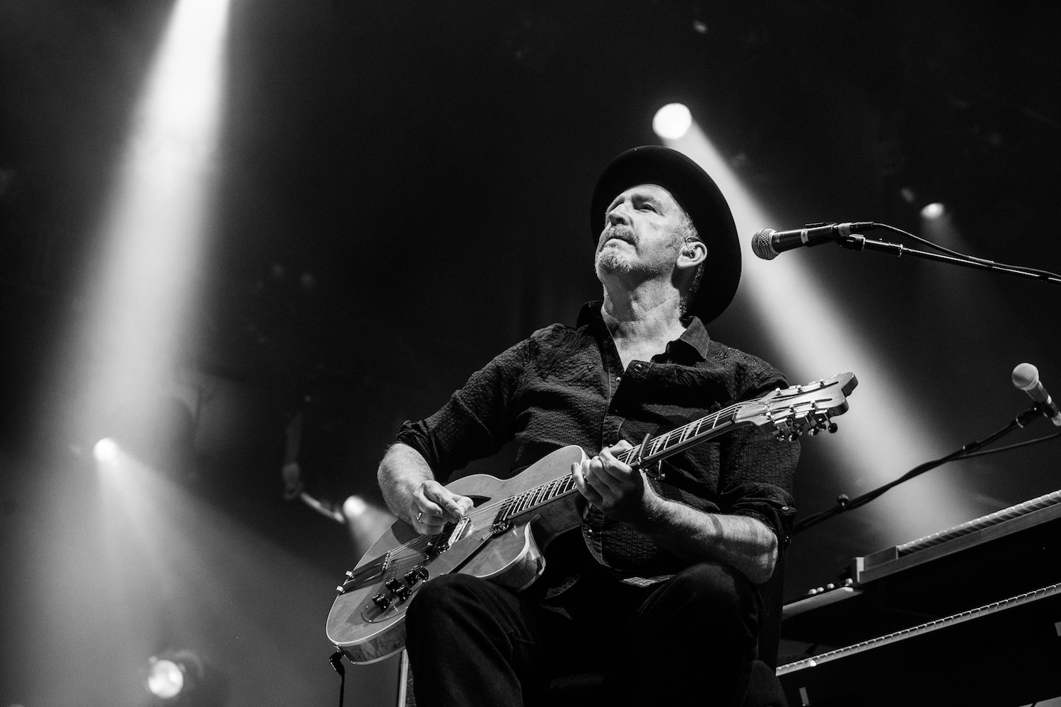 Black and white image of Jim Moginie playing guitar