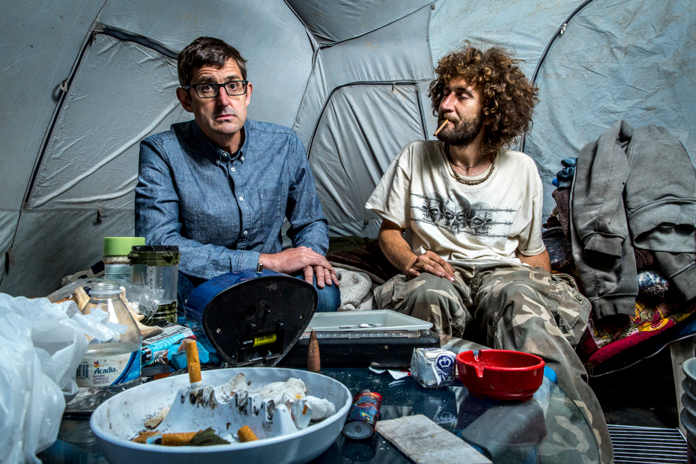 Theroux sits with Nate Walsh inside a tent. In the foreground you can see a full ashtray. The tent is messy and Walsh is unkempt.