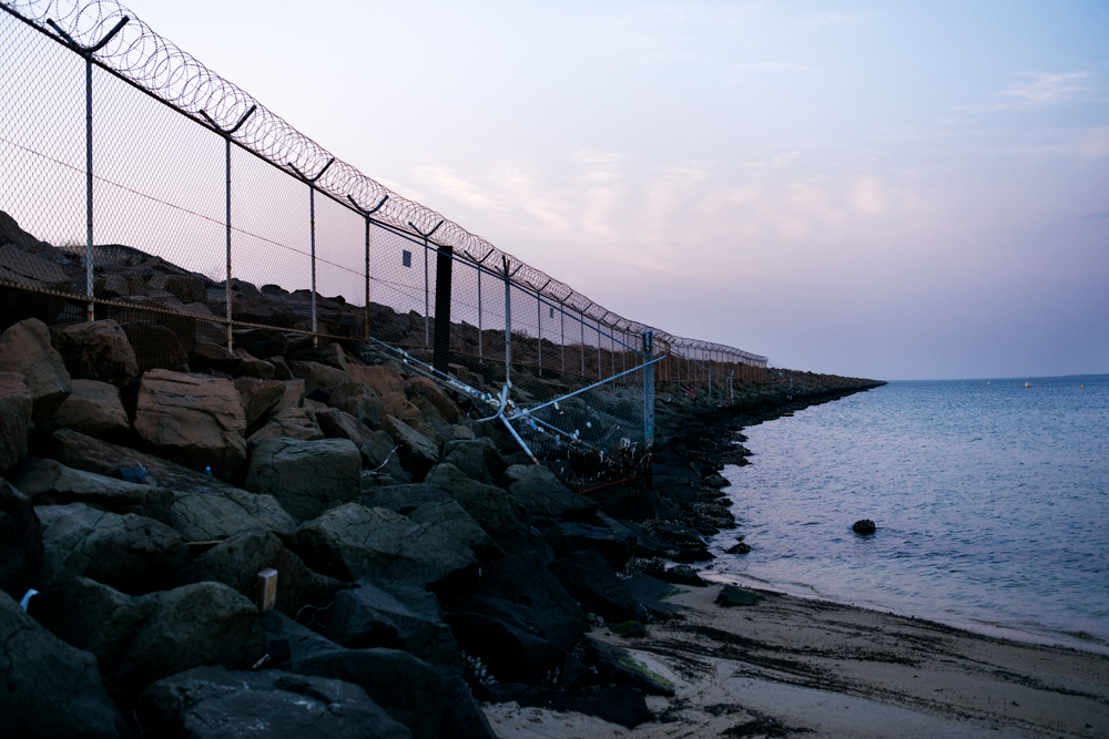 A fence with curled barb wire on top stretches along the rocks and into the distance, blocking access to Sydney Airport from the beach.