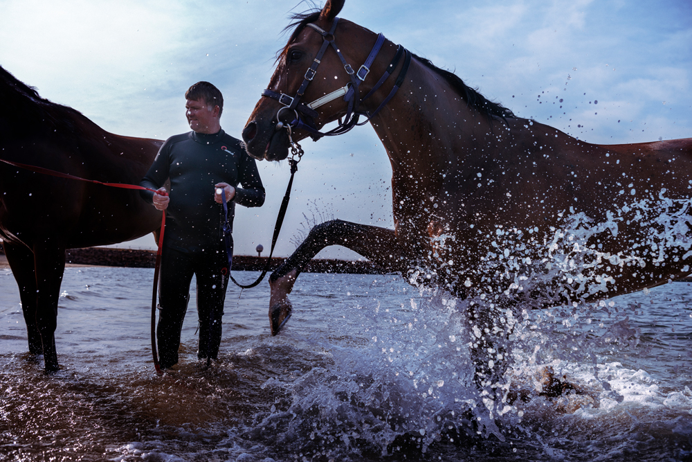 A trainer in a wetsuit holds the reins of two horses.