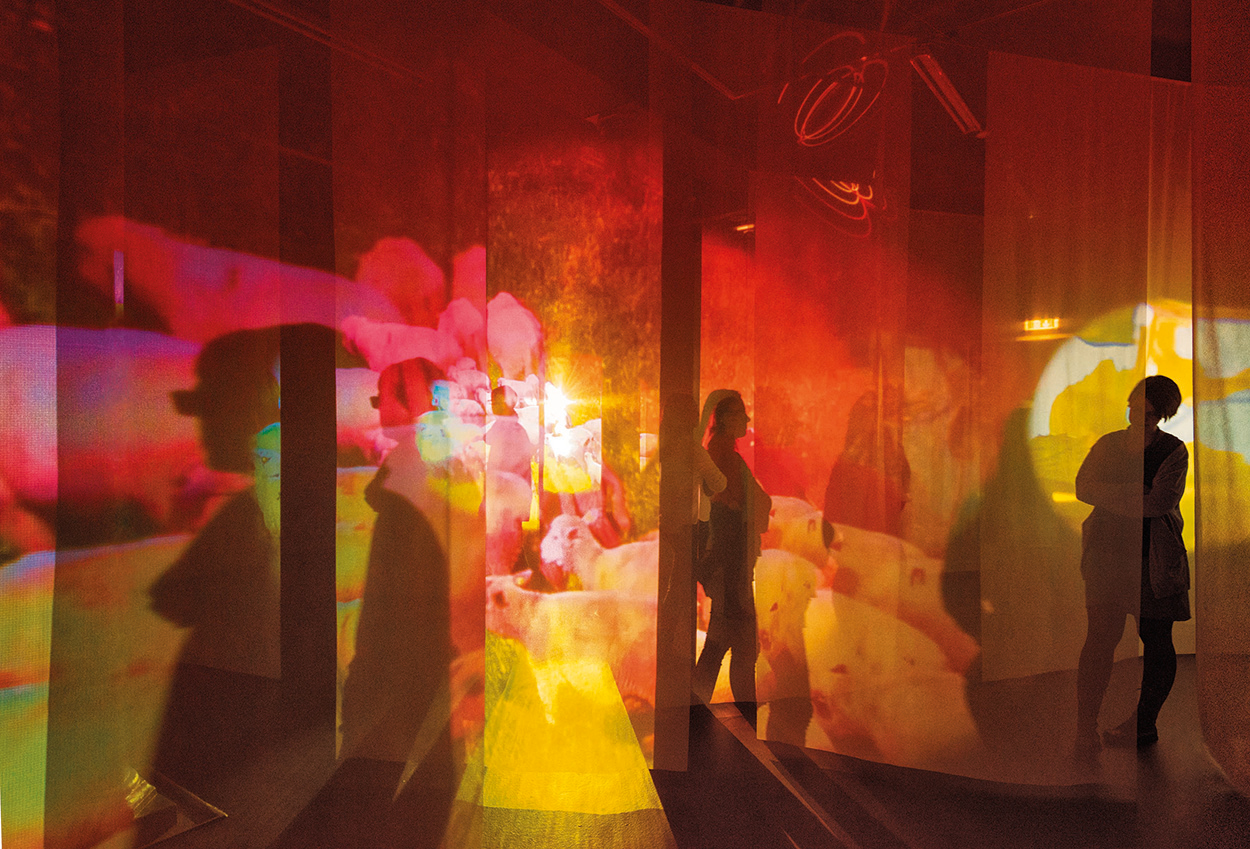 Figures walk between hanging cloth with red and orange images projected onto them.