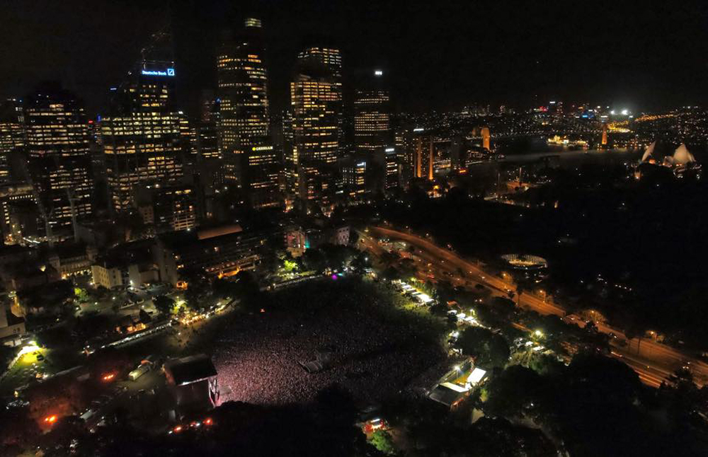 At the bottom of the image you can see the huge crowd gathered on the Domain, lit up by the light from the stage. Behind the crowd, taking up the rest of the image, is the CBD at night, with the Harbour Bridge lit up in the background.