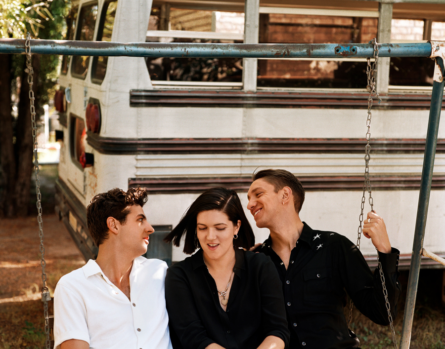 The three members of The xx sit together on a swing.