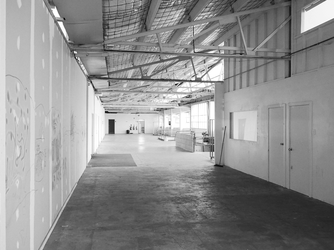 Birmingham Street Studios: a warehouse space stretches from the foreground of the photo into the distance, with exposed beams visible near the ceiling.