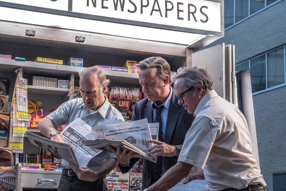 Ben Bradlee and two other newspapermen in front of a paper stand on the street, holding a copy of the New York Times.