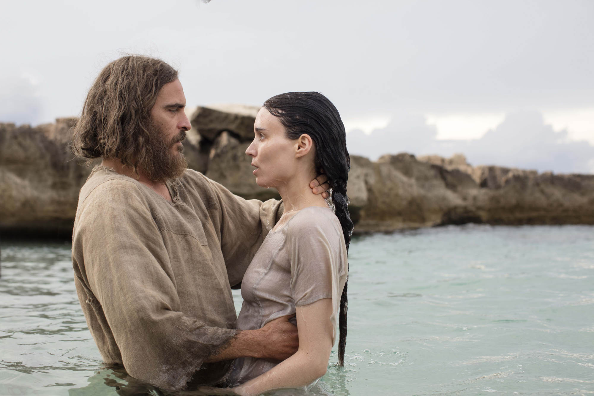 Jesus (Phoenix) and Mary (Mara) embrace in waist-deep water