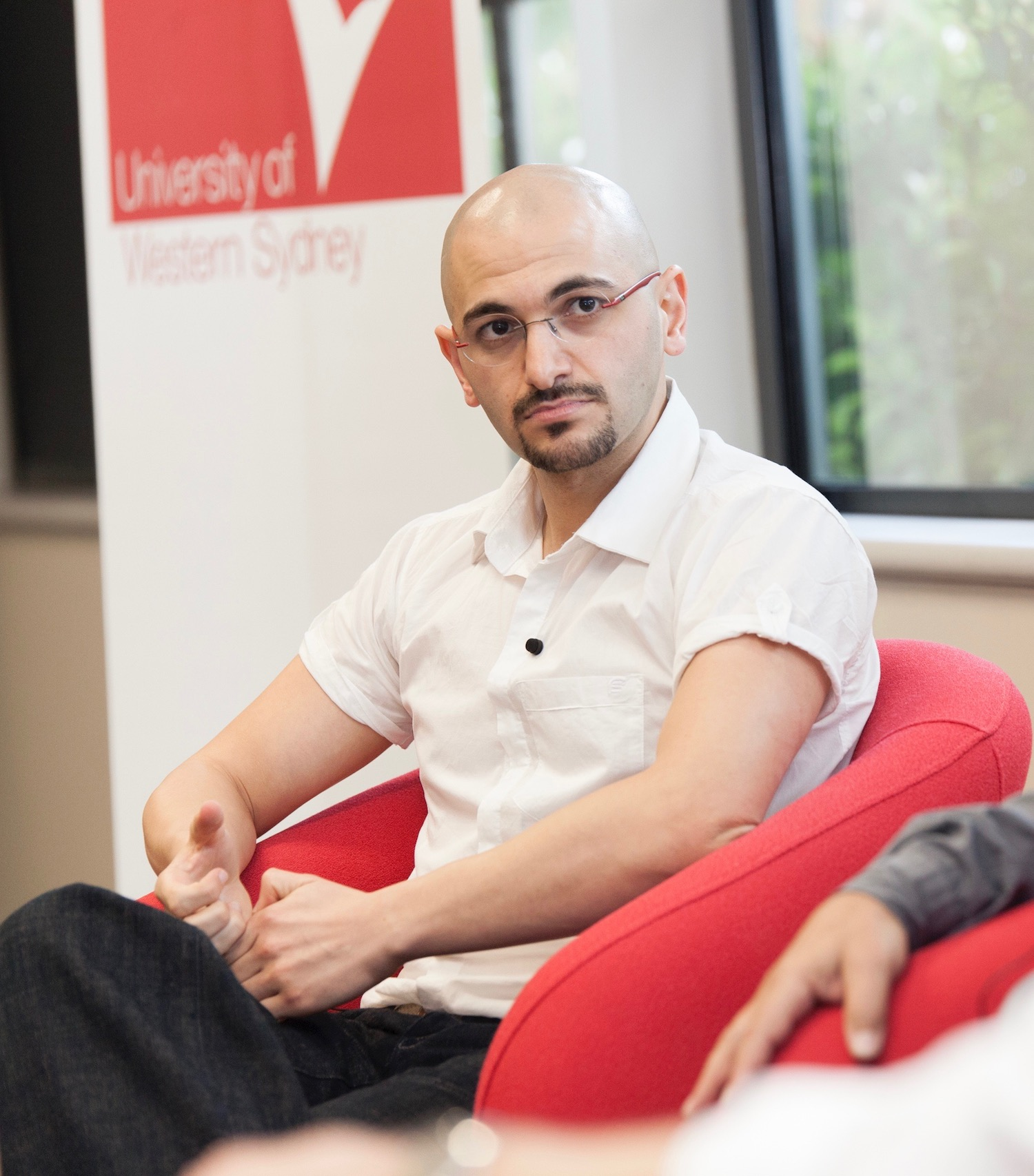 Michael Mohammed Ahmad sits in a red armchair at an academic event