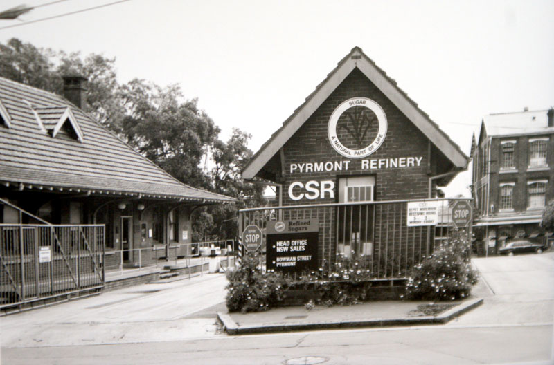 Black and white image of a gatehouse, with 'Pyrmont Refinery CSR' in bold white letters