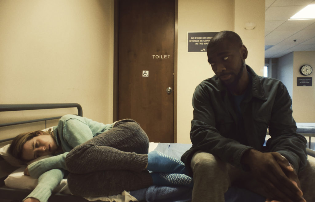 Foy curled on a bed, with Jay Pharoah as Nate Hoffman sitting next to her
