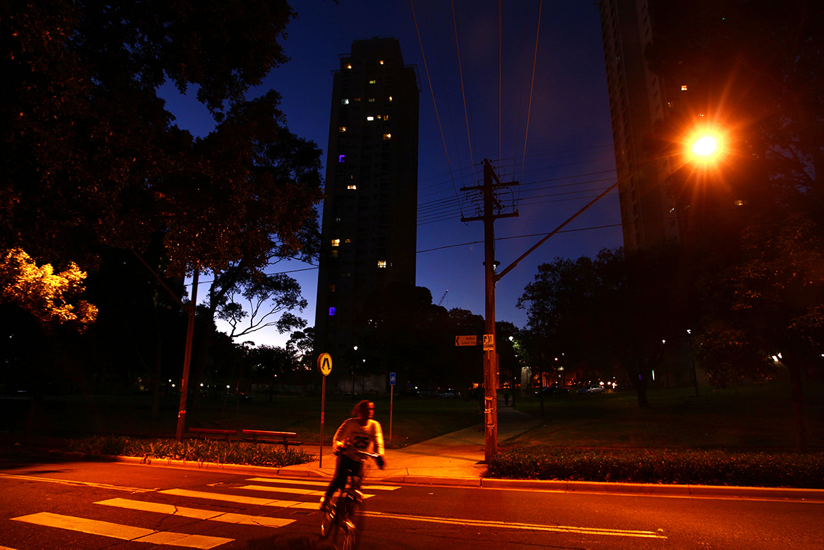 A resident rides a bike across a red-lit street, with the Waterloo towers rising up behind. Photography by Dean Sewell