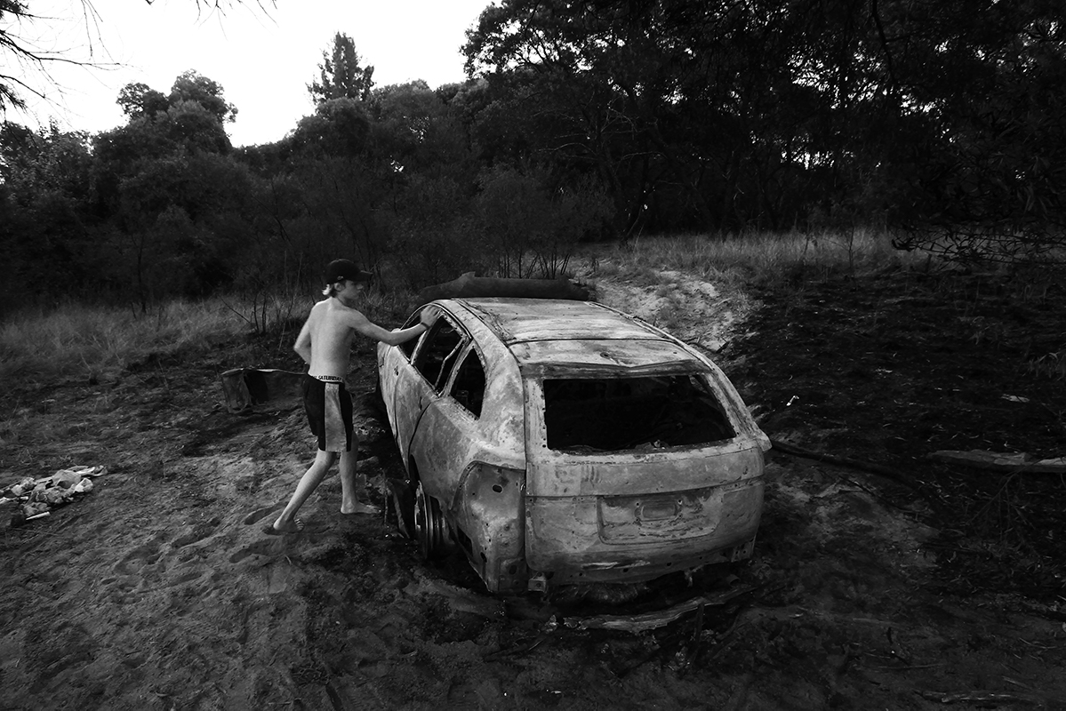 Boy with discarded and burnt car at Hawkesbury region