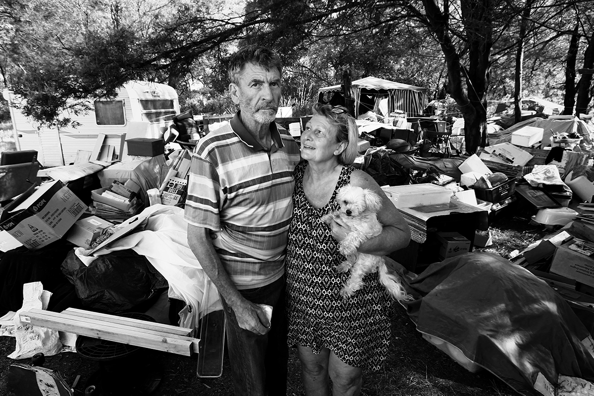 A man, woman and dog in front of lots of collected junk