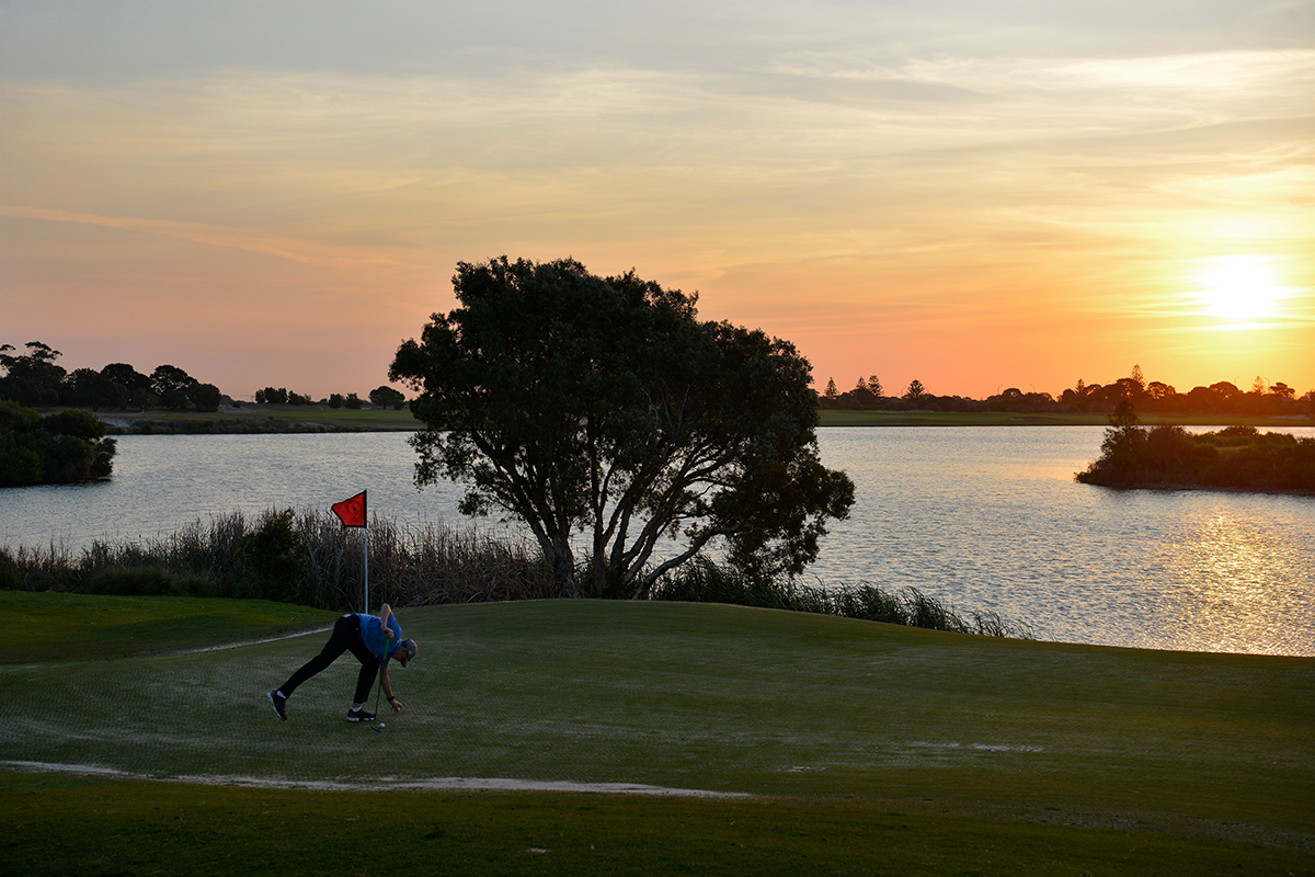 Sunset over the lake of a golf course. In the foreground a golfer bends to place his ball. Photography by Matthew Abbott