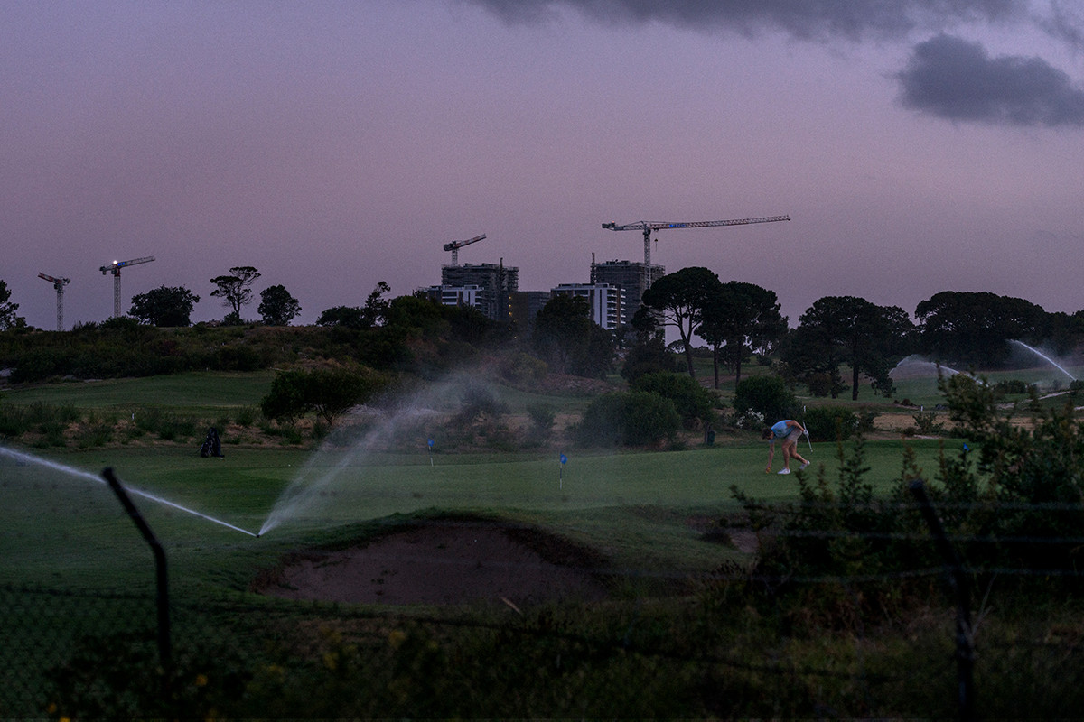 Dusk over a golf course. Cranes loom in the background. Photography by Matthew Abbott