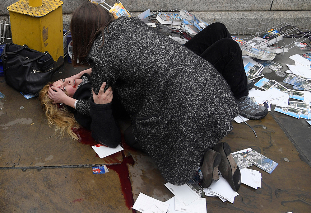 A passerby comforts an injured woman after Khalid Masood drove his car into pedestrians on Westminster Bridge in London, UK, killing five and injuring multiple others.