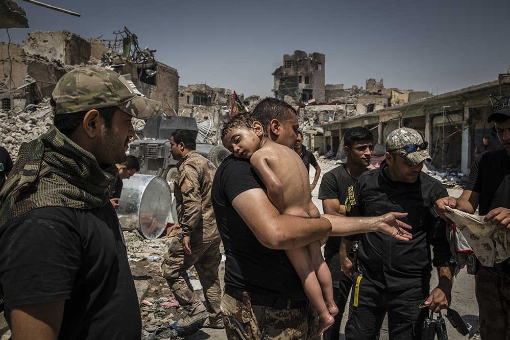 An unidentified young boy, who was carried out of the last ISIS-controlled area of the Old City by a man suspected of being a militant, is washed and cared for by Iraqi Special Forces soldiers. The soldiers suspected that the man had used the boy as a human shield in order to try to escape, as he did not know the child's name.